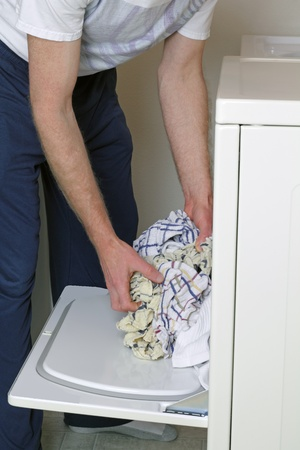 dryer: Man loading clothes into dryer dressed in casual clothes.
