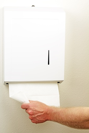A hand is pulling down and out a white folded sheet of disposable paper to dry hands from a wall box. photo