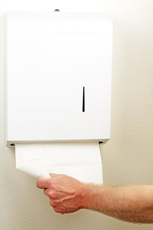 handt�cher: Eine Hand zieht nach unten und aus einem wei�en gefalteten Blatt Einweg Papier zu trockene H�nde von einer Wand-Box. Lizenzfreie Bilder