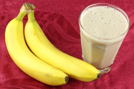 Two long yellow dessert fruit are next to a clear glass full of banana smoothie. photo