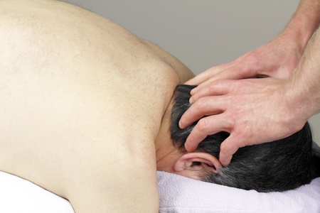 Mature man with graying black hair face down in a massage table receiving a scalp massage.