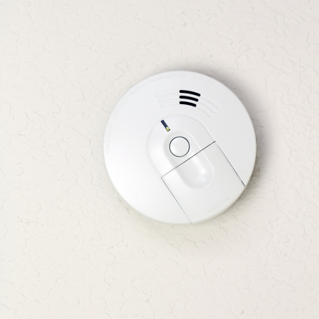 Small round battery operated device to warn residents of fire. photo