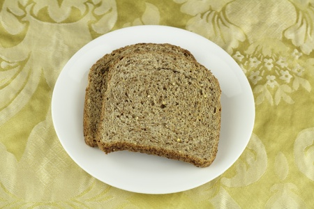 buttery: Two crisp whole sprouted grain and legume bread slices on a round white dish above a buttery yellow floral cloth placemat.