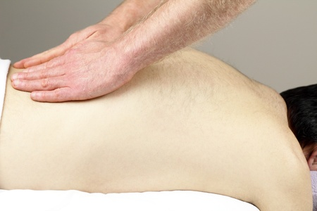 Mature male who is face down on a massage table is having his low back massaged by a masseur. Stock Photo - 8782050