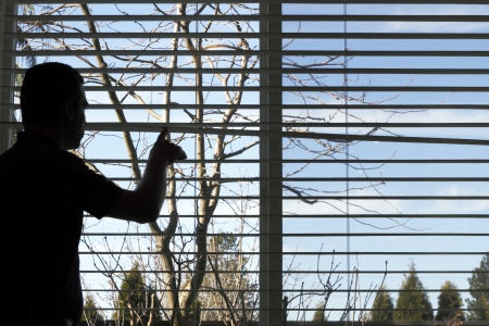 Silhouette of a man looking out a window, daydreaming of warmer weather.