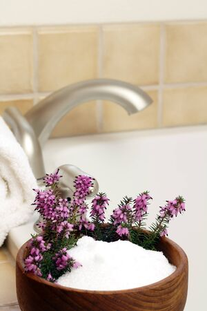 Epsom salts with purple heather flowers in a teak bowl make for a relaxing time.