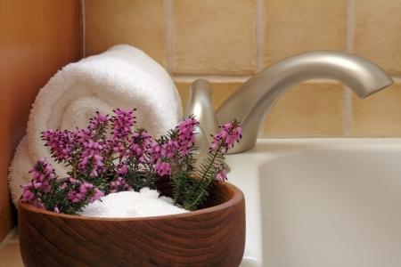 Epsom salts in a teak wood bowl with purple heather flowers and white bath towel on edge of a modern bath tub.