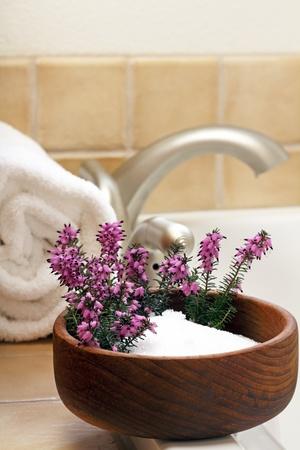 Pretty heather flowers in a bowl of Epsom salts on a bath tub edge ready to bathe.