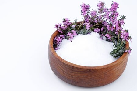 Beautiful purple heather flowers and white Epsom salts wait in a teak wood bowl on a white background.