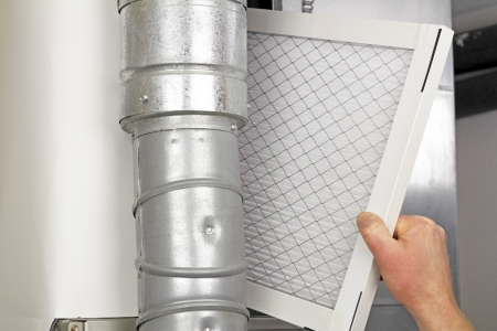 replacing: Male arm and hand replacing disposable air filter in residential air furnace. Stock Photo
