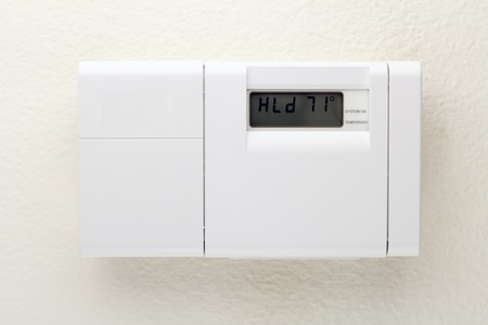 Outside of a white heating, ventilating, and air conditioning control panel on a wall. Stock Photo