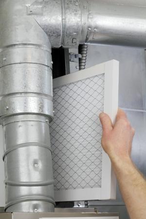 effizient: Eines Mannes Arm und Hand gesehen ersetzen Einweg Luft Filtern im Hause zentralen Luft-Ofen.