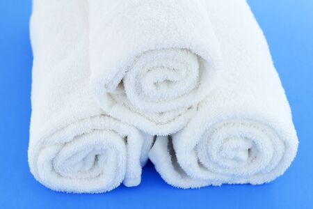 individually: Three large white cotton bath cloths rolled up individually and piled together on a blue background. Stock Photo