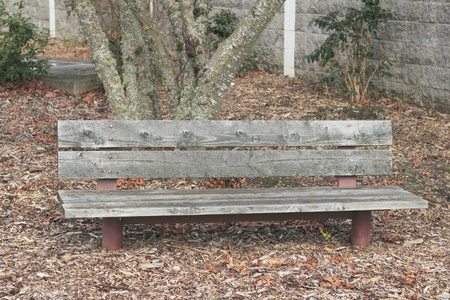 seating area: Wood seating area with faded red painted metal supports on a winter day.  Stock Photo