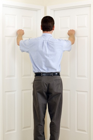 indecision: Man knocking on two doors that are side by side at the same time.
