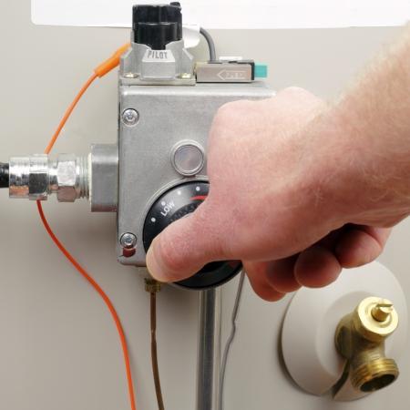 Main d'un homme en baissant le gaz de chauffe-eau domestiques température. Banque d'images