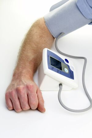 Male arm seen checking own blood pressure with an automatic monitor at home. Stock Photo
