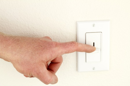 power switch: Hand of a man seen pressing down a sliding overhead lighting control on a wall