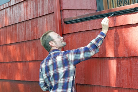 Man in his 40s adding paint detail to the side of a front porch.  photo