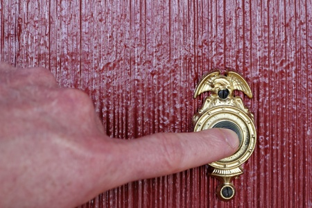 Finger of a mans hand ringing a gold and black door bell on a brick red house. Фото со стока