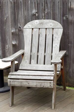 Old wood patio chair on an outside backyard deck with a weathered wood fence behind it. photo