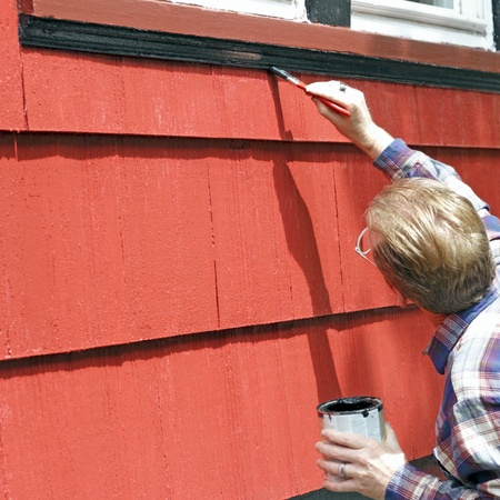 Man painting house window trim with black paint. photo