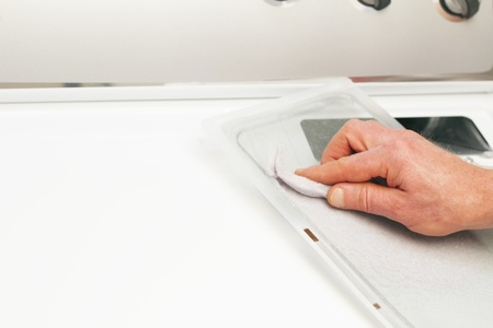Male hand cleaning the clothes dryer dirt collector of excess dust and fibers.