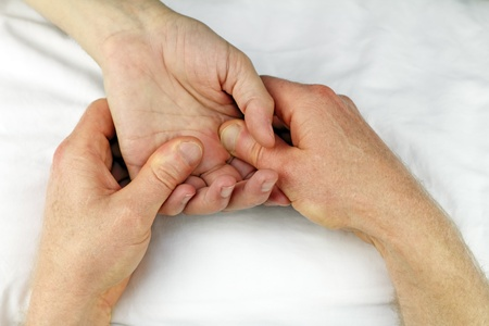 Male hand being massaged below fingers with two hands by a massage therapist.