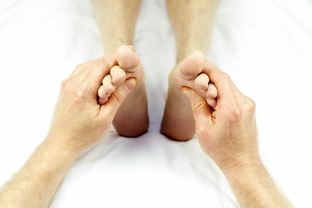 Male massage therapist hands giving a reflexology treatment to the soles of each foot of a patient.