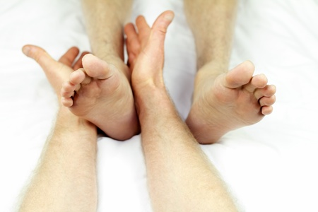 Man getting ankle rolling as part of a reflexology session from a male massage therapist. Stock Photo