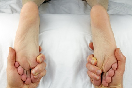 acupressure hands: Male getting both feet massaged with reflexology at the same time by the hands of a male massage therapist.