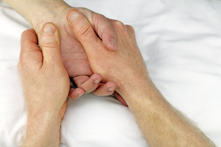 Male massage therapist hands massaging the hand of another man near the wrist. Stock Photo