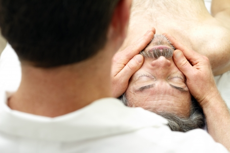 Mature man getting face massaged by a male massage therapist at a healthy spa. Stock Photo