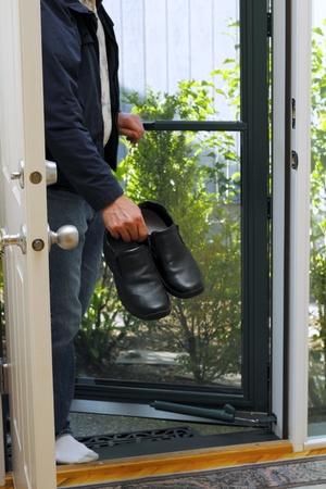 Man seen below shoulders entering front door with shoes in hand. photo