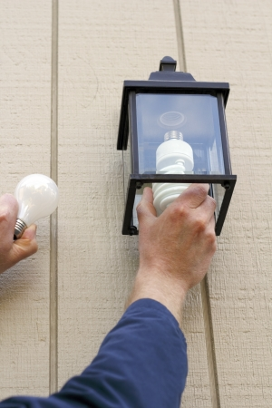Man carefully replacing an old incandescent lightbulb with a new CFL light in an outdoor fixture to save money when the lamp is on. 写真素材
