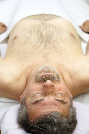goatee: Mature man lying face up on a white sheet covered professional massage table waiting for a massage to relax his sore muscles and to feel better.
