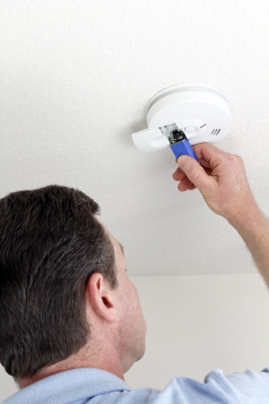 carefully: Man carefully replacing 9 volt battery in round white ceiling smoke alarm detector for the safety of his household. Stock Photo