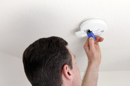 Man changing the 9 volt battery in a round white ceiling smoke alarm detector for fire safety.