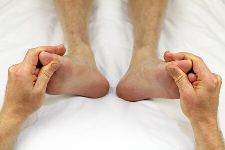 reflexologist: Big toes of both feet of an adult male receiving massage from a reflexologist as part of a treatment to promote circulation.