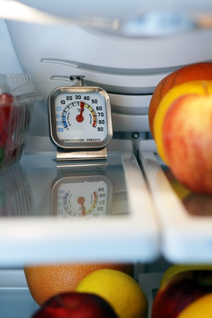 refrigerator with food: Refrigerator freezer temperature thermometer inside the top shelf of a cool food storage fridge to make sure perishables are kept safe and not too warm.