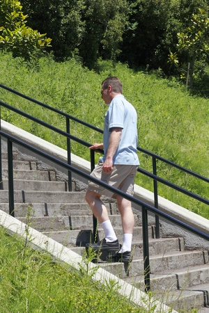 Man walking up stairs outside surrounded by landscape on a sunny summer day.