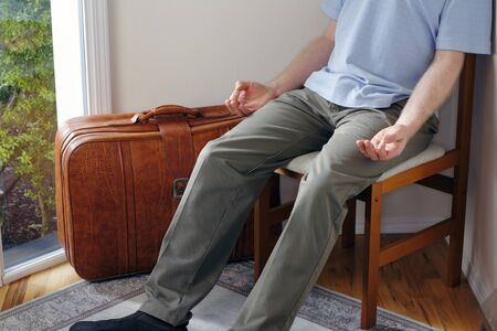 mindfulness: in a home foyer with a suitcase near door a male sits in a chair meditating before traveling to help have a peaceful journey. Stock Photo
