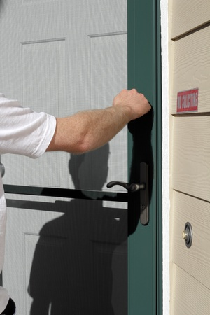 Male knocking on a residential front door during the day. Stock Photo