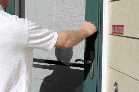 L'homme frappe à la porte d'entrée d'une maison sur une journée ensoleillée.