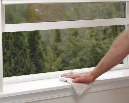 Hand dusting a window sill to reduce allergens in the home.