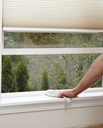 Male hand wiping off a window sill to reduce allergens in the home.