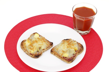 glass topped: Two healthy slices of sprouted grain bread topped with pizza toppings on a white plate and one glass of vegetable tomato juice on a round red place mat.