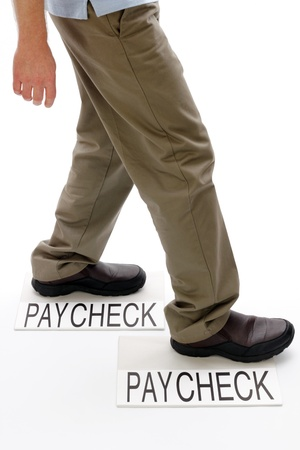 Person walking from one light gray rectangle paper packet marked paycheck to another with text saying paycheck on white ground.  Stock Photo