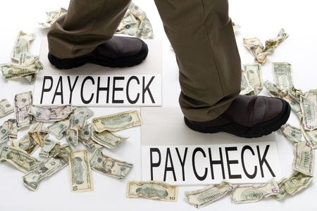 paycheck: Male legs walking from one paycheck to another with crumpled money scattered about on the floor.