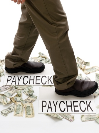 Person stepping from paycheck to paycheck with spent money lying crumpled on the ground.